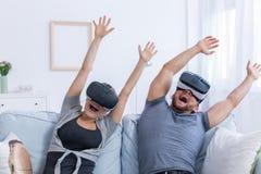 Man och kvinna som bär VR-exponeringsglas hemma royaltyfri fotografi