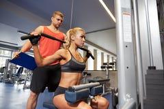 Man och kvinna som böjer muskler på idrottshallmaskinen Royaltyfri Foto