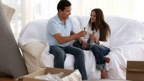Man och kvinna som dricker champagne för att fira deras nya hus lager videofilmer