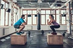 Man och kvinna som gör Squats på träsnitt i idrottshall arkivfoto