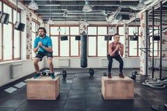 Man och kvinna som gör Squats på träsnitt i idrottshall fotografering för bildbyråer