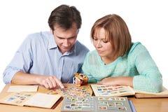 Man och kvinna som håller ögonen på en samling av portostämplar Fotografering för Bildbyråer