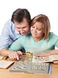 Man och kvinna som håller ögonen på en samling av portostämplar Arkivbild