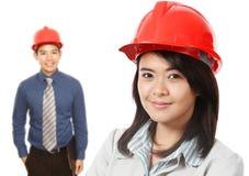 Man och kvinna som ha på sig Hardhats Arkivfoton