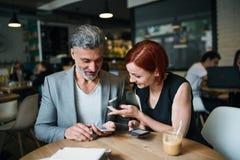 Man och kvinna som har affärsmöte i ett kafé, genom att använda smartphonen royaltyfria bilder