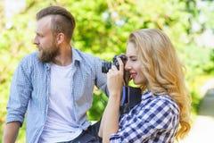 Man och kvinna som har det utomhus- datumet Flickaintelligens en fotokamera och hennes pojkv?n arkivbilder