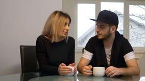 Man och kvinna som har ett kaffe och hemma pratar i köket i morgonen arkivfilmer