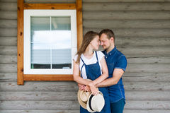 Man och kvinna som hemma står med ett stort träfönster, händelsebegreppet av en ung familj, arkivbilder