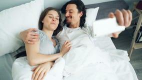 Man och kvinna som hemma som tar selfie i säng använder smartphonekameran som har gyckel arkivfilmer