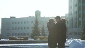 Man och kvinna som kramar och talar i vinterdag arkivfilmer