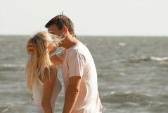 Man och kvinna som kysser på havet fotografering för bildbyråer