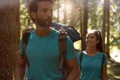 Man och kvinna som omkring ser, medan promenera fotvandra slingabanan i skogträn Grupp av vänfolksommar Arkivbilder