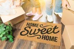 Man och kvinna som packar upp nära välkommet mattt för hem- sötsakhem, flyttning fotografering för bildbyråer