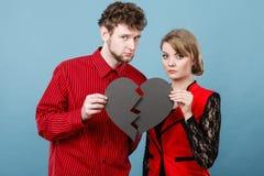 Man och kvinna som rymmer bruten hjärta arkivfoton