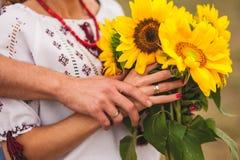 Man och kvinna som rymmer en bukett av solrosor ukrainskt bröllop Fotografering för Bildbyråer