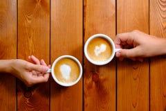 Man och kvinna som rymmer en kopp kaffe i kafét, bästa sikt Royaltyfri Fotografi