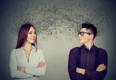 Man och kvinna som ser de som utbyter med många tankar royaltyfri foto