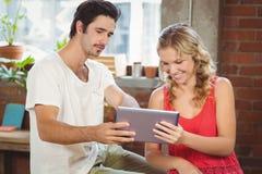Man och kvinna som ser den digitala minnestavlan Arkivfoto