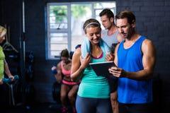 Man och kvinna som ser i minnestavladator på idrottshallen Royaltyfri Bild