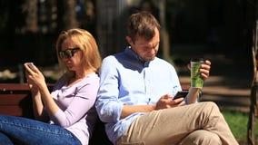 Man och kvinna som ser i olika riktningar som sitter på en bänk Alla ser hans mobiltelefon stock video