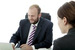 Man och kvinna som sitter på skrivbordet royaltyfri bild
