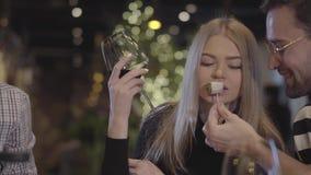 Man och kvinna som sitter på tabellen i den moderna restaurangen som äter och dricker alkohol som vilar med vänungdomar arkivfilmer