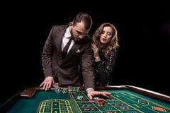 Man och kvinna som spelar på rouletttabellen i kasino arkivfoton