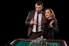 Man och kvinna som spelar på rouletttabellen i kasino royaltyfri bild
