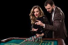 Man och kvinna som spelar på rouletttabellen i kasino royaltyfri fotografi