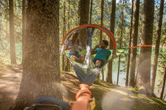 Man och kvinna som talar i det hängande tältet som campar i sjöskogträn under solig dag Grupp av vänfolksommar Royaltyfri Fotografi
