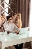 Man och kvinna som till varandra talar medan man som arbetar med en bärbar dator Arkivfoto
