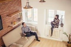 Man och kvinna som tillbaka sitter för att dra tillbaka och gör deras arbeten Arkivbild