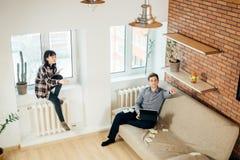 Man och kvinna som tillbaka sitter för att dra tillbaka och gör deras arbeten Royaltyfria Bilder