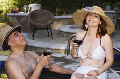 Man och kvinna som tycker om laughter, medan i ett varmt bada royaltyfri foto