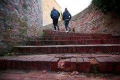 Man och kvinna som uppför trappan tillsammans kör Fotografering för Bildbyråer