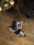 Man och kvinna som utför tango på trägolv Arkivbild