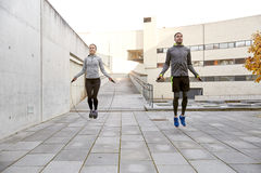 Man och kvinna som utomhus övar med hopp-repet Fotografering för Bildbyråer