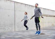 Man och kvinna som utomhus övar med hopp-repet Arkivfoto