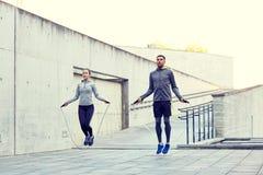 Man och kvinna som utomhus övar med hopp-repet Arkivfoton
