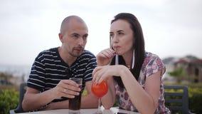 Man och kvinna som utomhus dricker coctailar i ett kafé arkivfilmer