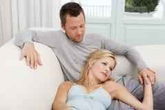 Man och kvinna som varar slö på sofaen Arkivfoton
