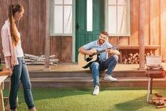 Man och kvinna som vilar på farstubron, man som spelar på gitarren Arkivbild