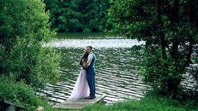 Man och kvinna, ungt lyckligt gift par nära sjön stock video