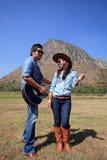 Man- och kvinnaanseende i lantgårdfältet som spelar gitarren och att dansa Arkivbild