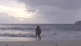 Man- och kvinnaanseende nära havet som håller ögonen på solnedgången och krama arkivfilmer
