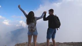 Man- och kvinnaanseende på kanten av den härliga kanjonen, victoriously outstretching armar upp Unga par av turister stock video