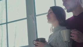Man- och kvinnaanseendet på fönstret och tycker om den romantiska atmosfären arkivfilmer