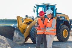 Man- och kvinnaarbetare på konstruktionsplats arkivbilder
