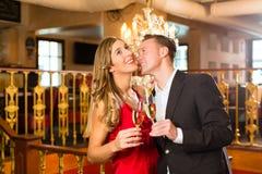 Man- och kvinnaavsmakningchampagne i restaurang Royaltyfri Foto