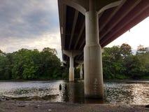 Man- och kvinnafiske i vadare under en bro, Lehigh flod, Laurys station, PA, USA royaltyfri fotografi